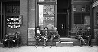 Men lounging outside a saloon and a Chinese laundry, 1910