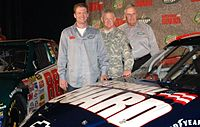 Dale Earnhardt Jr. (left) standing between two different paint schemes for the No. 88 Chevy, with Lt. Gen. Clyde A. Vaughn, director of the Army National Guard, and Rick Hendrick, in Dallas, where the announcement was made on September 19, 2007