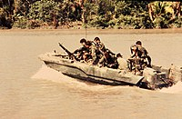 SEALs move down the Bassac River in a Seal Team Assault Boat (STAB) in Vietnam, 1967