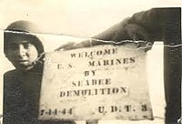Seabees in both UDT 3 and 4 made signs to greet the Marines assaulting Guam. However, Team 4 was able to leave theirs on the beach for the Marines to see that the Seabees had been there first. UDT 4 posted this sign again on the Hotel Marquee for its 25-year reunion.