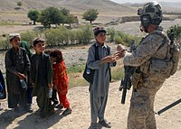 A US Navy SEAL, assigned to Special Operations Task Force-South East, greets children in a village in Uruzgan Province, 30 August 2012.
