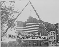 Photograph of U.S. flag and welcoming banner hung over a Washington street during ceremonies in honor of visiting Presidens aleman.