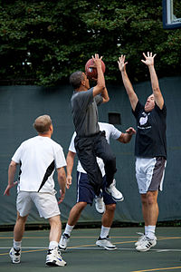 Obama takes a left-handed jump shot during a pickup game on the White House basketball court, 2009