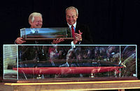 Carter (left) with a replica of the {{USS Jimmy Carter SSN-23 6}} with Secretary of the Navy John H. Dalton (right) at a naming ceremony, April 28, 1998