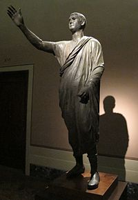 The Orator, c. 100 BC, an Etrusco-Roman bronze statue depicting Aule Metele (Latin: Aulus Metellus), an Etruscan man wearing a Roman toga while engaged in rhetoric; the statue features an inscription in the Etruscan language