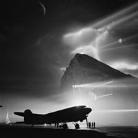 Shown here during the Second World War, a Douglas Dakota of BOAC is silhouetted at Gibraltar by the batteries of searchlights on the Rock, as crews prepare it for a night flight to the United Kingdom