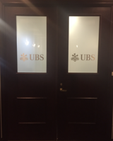 An entrance to a UBS Wealth Management office in Milan, Italy. With a strike-plated door and frosted glass, its purpose is to provide security and banking discretion.
