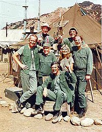 The cast of M*A*S*H from season 8 onward (clockwise from left): Mike Farrell, William Christopher, Jamie Farr, David Ogden Stiers, Loretta Swit, Alan Alda, and Harry Morgan
