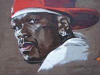 """Graffiti depicting US rapper 50 Cent. Larry Nager of The Cincinnati Enquirer wrote that 50 Cent has """"earned the right to use the trappings of gangsta rap – the macho posturing, the guns, the drugs, the big cars and magnums of champagne. He's not a poseur pretending to be a gangsta; he's the real thing."""""""