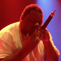 Biz Markie is noted for his beatboxing skills. He is holding the mic close to his mouth, a technique beatboxers use to imitate deep basslines and bass drums, by exploiting the proximity effect.
