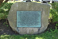 Stone plaque marking the site of the first public school in America in Dedham, Massachusetts