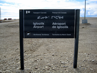 Entrance sign to Igloolik Airport, with text in English, French, and Inuktitut