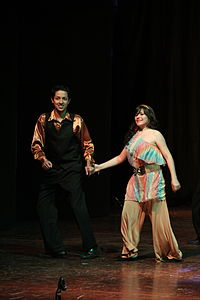 Disco dancers typically wore loose slacks for men and flowing dresses for women, which enabled ease of movement on the dance floor.