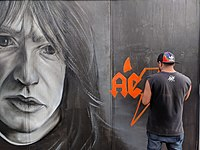 A street artist painting a Young portrait one day after the musician died
