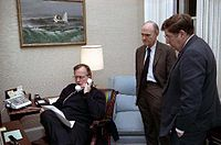Bush speaks on the telephone regarding Operation Just Cause as General Brent Scowcroft and Chief of Staff John H. Sununu look on, 1989