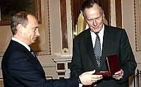 """Bush (right) with Russian president Vladimir Putin as he receives the Jubilee Medal """"60 Years of Victory in the Great Patriotic War 1941–1945"""" from Putin in 2005."""