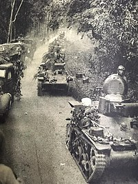 Japanese Type 97 Te-Ke tanks, followed by their bicycle infantry, advancing during the Battle of Kampar, December 1941