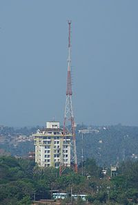 alt=White, multistory building with tall red-and-white tower in front|AIR tower in Mangalore, Karnataka