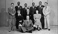 """Photo of 1948 Raleigh Cigarette Program cast: Standing: Pat McGeehan, The Four Knights, David Rose (orchestra leader). Seated: Verna Felton (""""Grandma"""" to Skelton's """"Junior"""" character), Rod O'Connor (announcer), Lurene Tuttle (""""Mother"""" to Skelton's """"Junior"""" character). Front: Skelton"""