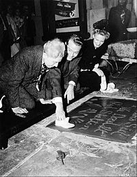 """Skelton's imprint ceremony at Grauman's Chinese Theatre, June 18, 1942. His wife, Edna, is on his left. Skelton also imprinted """"Junior's"""" shoes along with the message, """"We Dood It!"""". Theater owner Sid Grauman is in foreground of photo."""