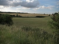 Durrington Walls, as seen from the south of the monument. It is bisected here to the left by one of the two roads that now cross the prehistoric site.