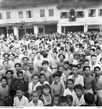 Crowds throng a street in Kuching to witness the arrival of Australian Imperial Force (AIF) on 12 September 1945.