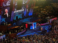 """Kennedy speaks during the first night of the 2008 Democratic National Convention in Denver, Colorado, while delegates hold signs reading """"KENNEDY"""""""