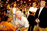 Clinton greets a Hurricane Katrina evacuee, September 5, 2005. In the background, second from the right, is then-Senator Barack Obama.