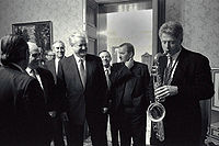 Clinton plays the saxophone presented to him by Russian president Boris Yeltsin at a private dinner in Russia, January 13, 1994