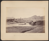 One of five bridges that crossed Kabul River during the Second Anglo-Afghan War (1879-1880) era. Soldiers a pictured atop the bridge while people walk along the road in the distance and in the right foreground people sit or squat on the bridge while soldiers ride behind them. Bala Hissar (High Fort) is in the background just visible through the heat haze and trees. It was the locus of power in Kabul for many centuries and the site of fierce fighting during the war. It was partly destroyed in October–December 1879 when Sir Frederick Roberts occupied the city at the head of the Kabul Field Force