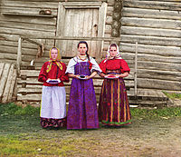 Young Russian peasant women in front of a traditional wooden house (c.1909 to 1915) taken by Prokudin-Gorskii