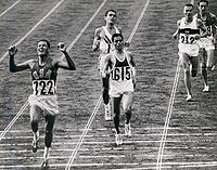 Billy Mills crosses the finish line at the end of the 10,000-meter race at the 1964 Tokyo Olympics.