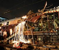 Railway workers cutting a damaged part of the bomb-damaged coaches
