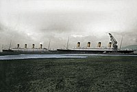 Belfast, March 1912: Olympic (right) leaving the Tompson dry dock after making repairs to her propeller blade. Titanic (left) moored at the pier, during her final conditioning phase (coloured picture)