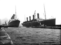 Olympic (left) being manoeuvred into dry dock in Belfast for repairs on the morning of 2 March 1912 after throwing a propeller blade. Titanic (right) is moored at the fitting-out wharf. Olympic would sail for Southampton on 7 March, concluding the last time the two ships would be photographed together