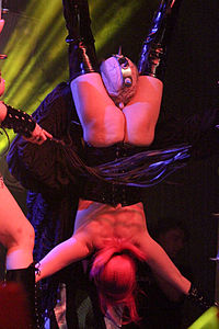 Sexual activity may occur in BDSM, but it is not essential part of BDSM. Photo shows erotic humiliation of sexual nature being performed at Wave-Gotik-Treffen music festival, Germany, 2014. The submissive woman is stripped naked, hung upside down, whipped and a master doing sexual roleplay of a devil forces himself on her to cause vagina torture.
