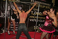 Flogging of a bound man by a dominatrix at the Exxxotica adult event, United States, 2009