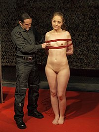 A male bondage rigger demonstrates to the audience how to do rope bondage at the 2015 BoundCon event in Germany. The bondage technique used here is box tie, a basic form of arm and breast bondage.