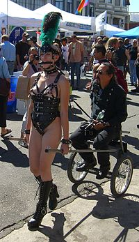 A sulky cart drawn by a pony-girl, an example of petplay at the Folsom Parade, 2005. She is wearing a bit gag and a neck collar, to which are attached a ring of O and a leash. To her nipples are attached bells. All these symbols are indicative of her roleplaying a BDSM pet slave.