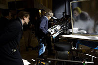 Director Christopher Nolan (far left) and actor Heath Ledger (in make-up) filming a scene in The Dark Knight with an IMAX camera