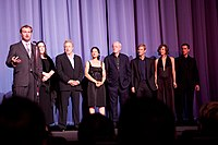 Cast and crew of The Dark Knight at the European premiere in London. From left to right: Director Christopher Nolan, producers Emma Thomas and Charles Roven, actors Monique Gabriela Curnen, Michael Caine, Aaron Eckhart, Maggie Gyllenhaal and Christian Bale.