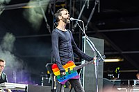 Stefan Olsdal performing in 2014, using a rainbow bass guitar; the rainbow is a well-known LGBT symbol.