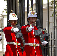 alt=Two soldiers in red dress uniforms Changing of the guard, Royal Gibraltar Regiment (2012)