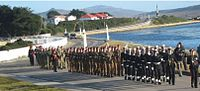 alt=Line of soldiers near water Falkland Islands Defence Force on parade in June 2013