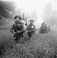 Led by their piper, men of the 7th Battalion, Seaforth Highlanders (part of the 46th (Highland) Brigade), advance during Operation Epsom on 26 June 1944