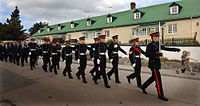 alt=Soldiers marching down a street in black uniforms Detachment of the Falkland Islands Defence Force in ceremonial dress