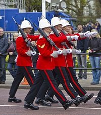 alt=Four soldiers marching in red-and-blue dress uniforms Royal Gibraltar Regiment in London, April 2012