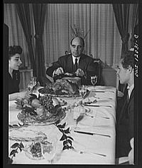 Dr. Mordecai Johnson, president of Howard University, serving portions of Thanksgiving turkey to members of his family in 1942