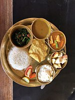 A dal-bhat thali with boiled rice, lentil soup, fried leafy greens, vegetable curry, yoghurt, papad and vegetable salad