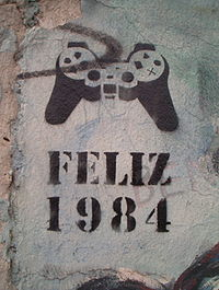 """Happy 1984"" (in Spanish or Portuguese) stencil graffito, denoting mind control via a PlayStation controller, on a standing piece of the Berlin Wall, 2005."